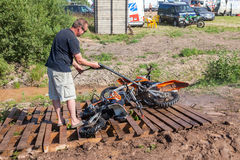 Équipez laver un vélo de course après la concurrence dans le motocross Photographie stock libre de droits