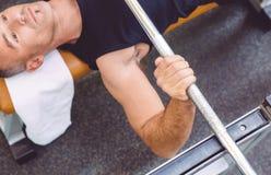 Équipez le barbell de levage de main sur une formation de banc à presse image libre de droits