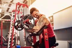 Équipez le bodybuilder faisant l'ensemble d'un exercice de barbell dans un gymnase Tir en temps réel Image stock