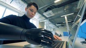 Équipez le bras prosthétique du ` s dactylographiant sur un ordinateur portable Concept robotique de bras de cyborg banque de vidéos