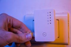 Équipez le câble d'Ethernet d'insertion dans le dispositif de supplément de WiFi qui est dedans Photos libres de droits