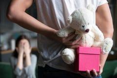 Équipez le cadeau de dissimulation faisant la surprise romantique pour l'épouse, plan rapproché arrière Images libres de droits
