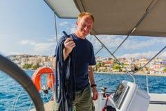 Équipez le capitaine à son bateau à voile, contrôles se transportent dans la course de yacht de mer photo stock