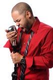 Équipez le chant dans le microphone de cru Photo stock