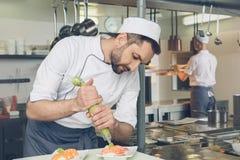 Équipez le chef de restaurant japonais faisant cuire dans la cuisine photographie stock libre de droits