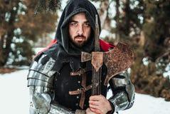 Équipez le chevalier dans l'habillement historique avec une hache Photo stock
