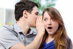 Équipez le chuchotement dans l'oreille de son épouse étonnée Photographie stock libre de droits