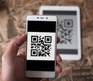 Équipez le code de qr de balayage de main du comprimé utilisant le téléphone portable image libre de droits