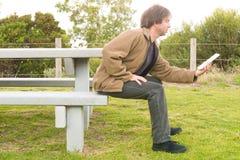 Équipez le comprimé de visionnement tandis qu'assis sur un banc de parc Image stock