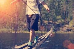 Équipez le croisement par le pont accrochant dans la bonne journée ensoleillée au-dessus du lac Image stock