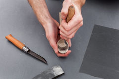 Équipez le découpage de mains d'une cuillère en bois avec le couteau de crochet sur le fond gris avec l'émeris Photographie stock