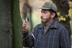 Équipez le détective avec une barbe étudiant le tronc d'arbre dans la forêt d'automne Image stock