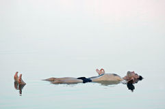 Équipez le flottement dans une eau vitreuse de mer morte photographie stock libre de droits
