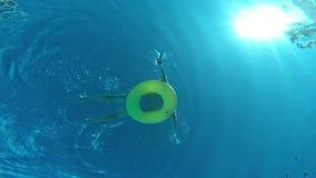 Équipez le flottement sur l'anneau gonflable dans la piscine, vue d'eau du fond clips vidéos