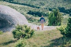 Équipez le fonctionnement sur le champ avec le chien de taureau Photo stock