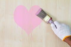 Équipez le gant blanc de port de main du ` s tenant le vieux pinceau grunge et peignant le coeur rose sur le mur en bois Photos stock