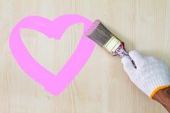 Équipez le gant blanc de port de main du ` s tenant le vieux pinceau grunge et peignant le coeur rose sur le mur en bois Photographie stock