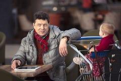 Équipez le grand-papa de papa au magasin avec le bébé dans le chariot Photographie stock libre de droits