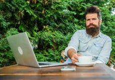 Équipez le hippie barbu font la pause pour le café de boissons et pensent tandis que reposez-vous avec l'ordinateur portable Cass photo libre de droits