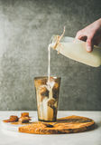 Équipez le lait se renversant de main du ` s aux glaçons de café en verre Photos stock
