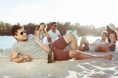 Équipez le mensonge sur la plage sablonneuse tandis que ses amis se reposant derrière sur la rive Images stock
