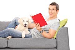 Équipez le mensonge sur le sofa avec le chiot et lire un livre Image libre de droits