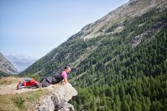 Équipez le mensonge sur le précipice regardant le paysage montagneux photo stock