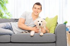 Équipez le mensonge sur un divan avec un chiot de Labrador à la maison Images stock
