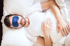 Équipez le mensonge sur un lit avec le masque de sommeil Image stock