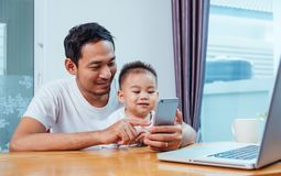 Équipez le père travaillant sur l'ordinateur portable et employant le techn de smartphone photo stock