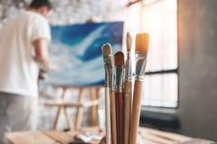 Équipez le peintre travaillant dans l'atelier derrière la toile et le dessin Les brosses se ferment sur la table en bois dans le  Photo stock