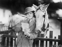 Équipez le penchement contre une barrière lisant une lettre à son cheval (toutes les personnes représentées ne sont pas plus long photos libres de droits