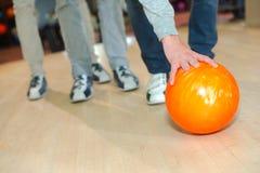Équipez le penchement vers le bas pour prendre la boule de bowling photo libre de droits