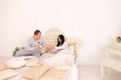 Équipez le petit déjeuner apporté de café de fille dans le lit, soins de mari pour l'épouse photographie stock libre de droits
