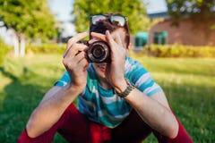 Équipez le photographe prenant des photos en parc au coucher du soleil Plan rapproché d'appareil-photo Le jeune type apprécie son photo stock