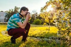 Équipez le photographe prenant des photos des fleurs en parc au coucher du soleil Le jeune type apprécie son passe-temps dehors photos stock