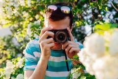 Équipez le photographe prenant des photos des fleurs en parc au coucher du soleil Le jeune type apprécie son passe-temps dehors P photo stock