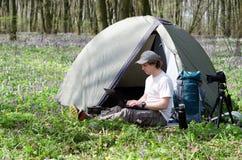 Équipez le photographe travaillant dehors dans un camp de tente Image stock