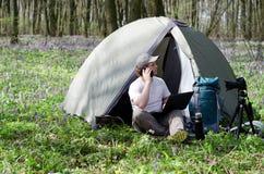 Équipez le photographe travaillant dehors dans un camp de tente Photographie stock