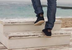 Équipez le pied du ` s marchant sur l'échelle en bois Image stock