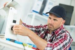 Équipez le réparateur travaillant dans l'atelier et réparant le dispositif Photos stock