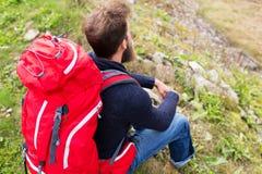 Équipez le randonneur avec le sac à dos rouge se reposant sur la terre Images libres de droits
