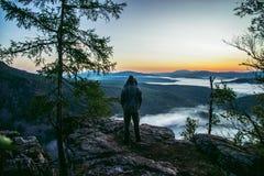 Équipez le randonneur reculant sur la crête des montagnes et appréciez pour voir la belle vue de paysage des roches et de la brum image libre de droits