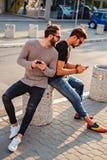 Équipez le regard dans le téléphone au-dessus de l'épaule de son ami Photo stock