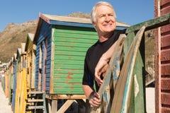 Équipez le regard parti tout en se tenant contre des huttes de plage Images stock