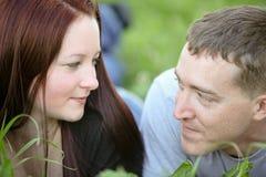 Équipez le regard profondément dans l'amour dans le pré avec sa femme Photographie stock libre de droits