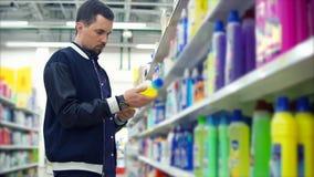 Équipez le regard sur la bouteille du détergent de lavage dans le mail et lire le label banque de vidéos
