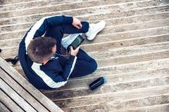 Équipez le repos après la séance d'entraînement de fonctionnement ou de forme physique et à l'aide du téléphone portable et l'eau Image libre de droits