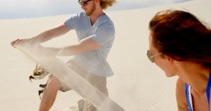 Équipez le sable de frottage au-dessus du panneau de sable tandis que femme observant 4k banque de vidéos