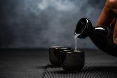 Équipez le saké de versement dans la cuvette sirotante photo libre de droits